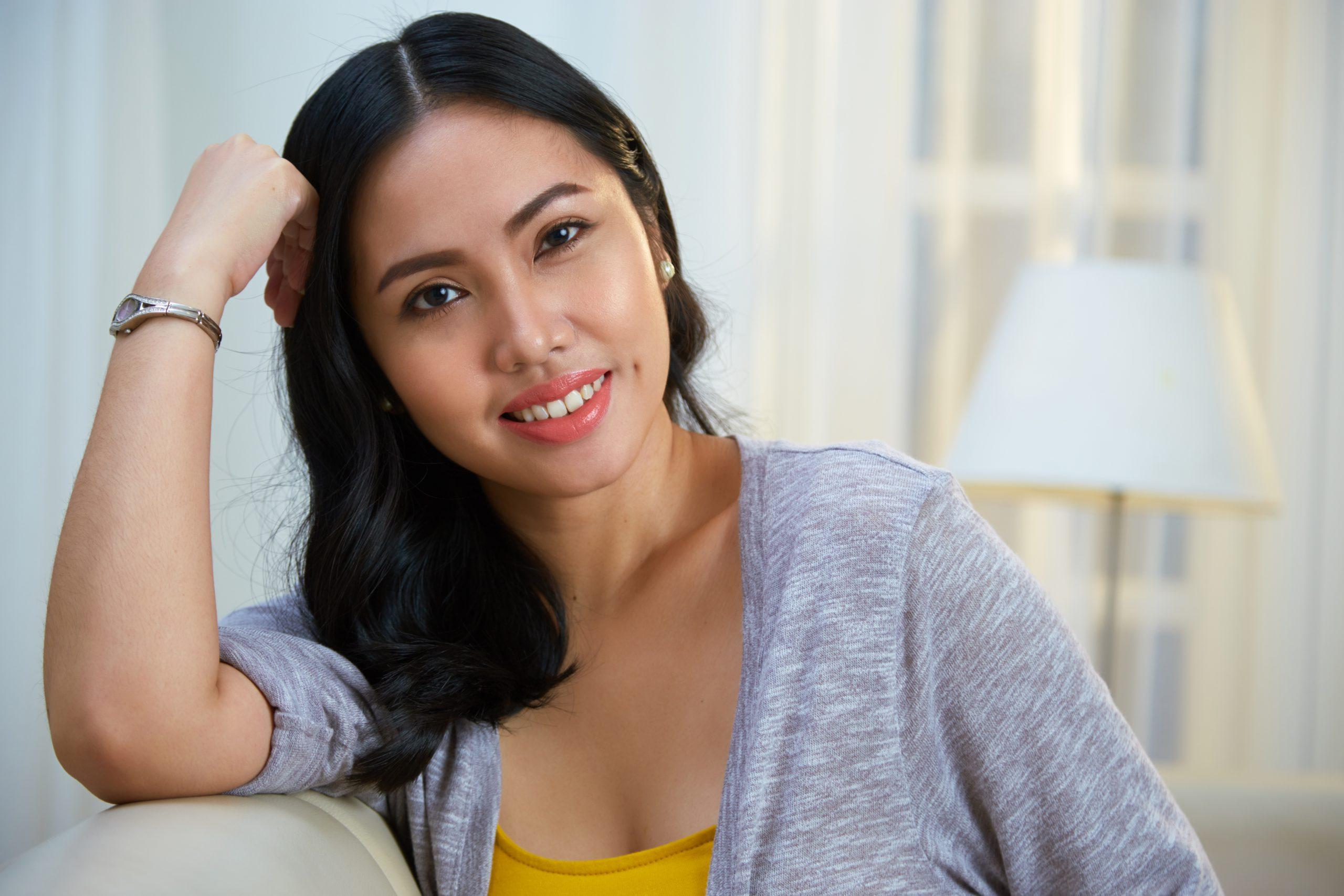 Charming Filipino woman leaning on sofa back